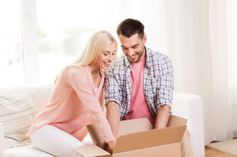 48902701 - happy couple opening cardboard box or parcel at home